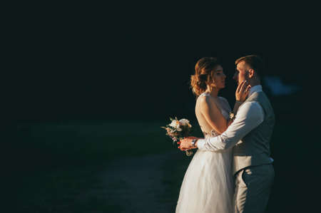 the bride and groom at sunset on a dark background