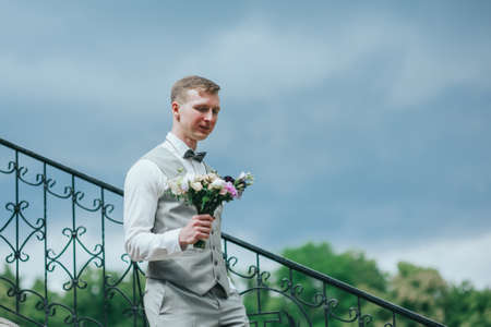 Stylish groom holding a tender pink wedding bouquet Stock Photo