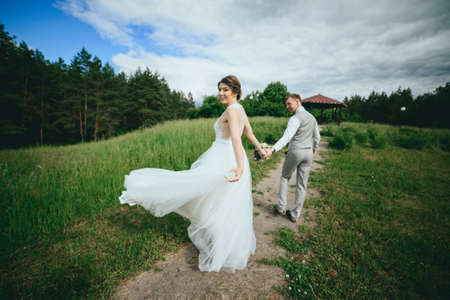 Wedding couple, bride, groom walking and posing on pier
