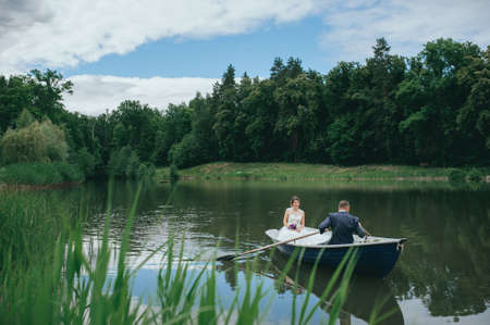 beautiful young wedding couple, blonde bride with flower and her groom just married on small boat at pond