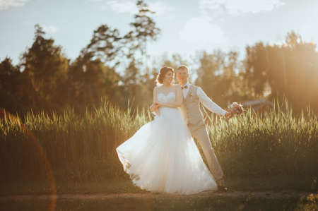 the bride and groom posing at sunset. loft. rustic. boho.