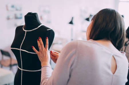the girl tailor takes measurements on the mannequin