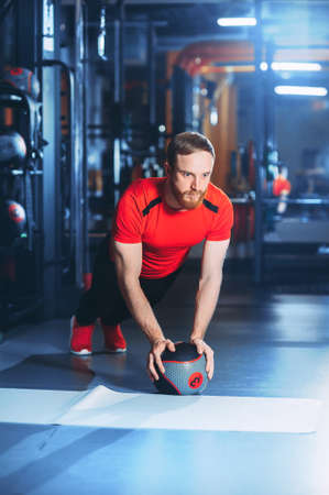 Muscular beards man doing intense core workout in gym. doing core exercise on fitness mat with medicine ball in health club. Stock Photo