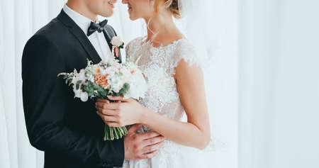stijlvolle bruidegom met baard en mooie bruid poseren in hotel. geïsoleerd. witte achtergrond Stockfoto