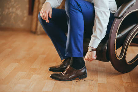 the groom wears shoes on wedding preparations