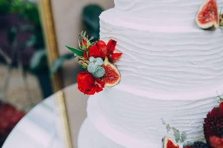 beautiful tiered wedding cake with fresh flowers Stock Photo