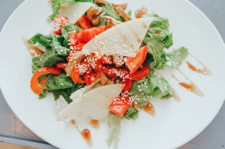 Green salad made with arugula, tomatoes, cheese mozzarella balls and sesame on plate, on color wooden background 写真素材