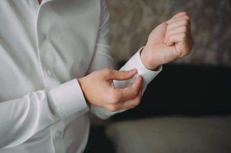 groom buttoning the shirt. wedding preparations. white shirt