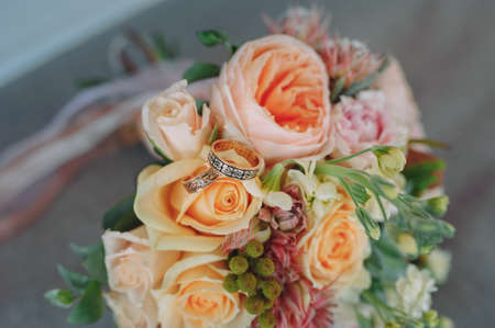 beautiful gold wedding rings on the brides preparations. rings on a bouquet Stock Photo