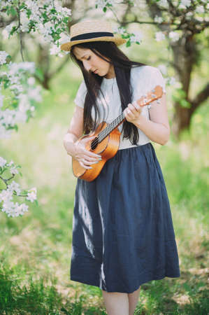 a beautiful girl in a straw hat plays a ukulele in a blossoming Apple orchard