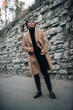 stylish guy in a coat and cap posing on the street