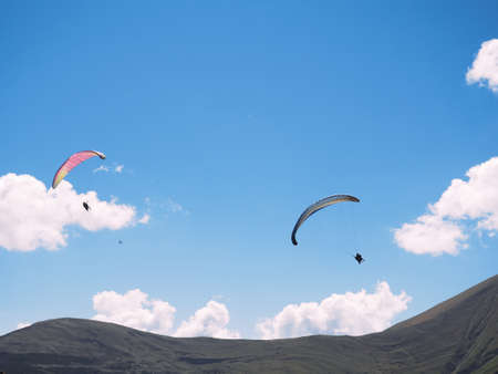 paragliders against the blue sky and mountains