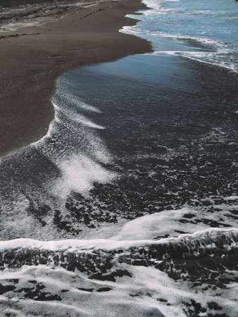 Sea wave on sand beach photo background. black sand
