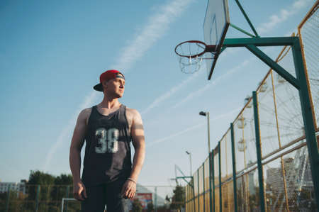 guy in a red baseball cap on the basketball court