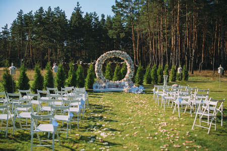 Beautiful wedding archway. Arch decorated with peachy and silvery cloth and flowers 스톡 콘텐츠