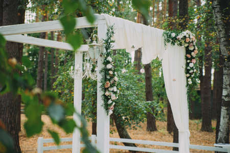 Beautiful wedding archway. Arch decorated with peachy and silvery cloth and flowers 写真素材