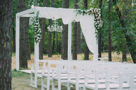 Beautiful wedding archway. Arch decorated with peachy and silvery cloth and flowers Stock fotó