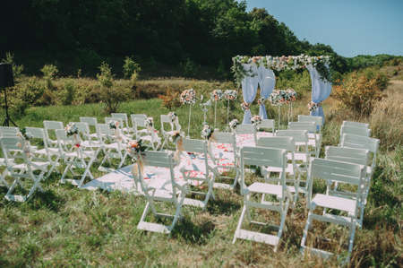 Wedding arch decorated with cloth and flowers outdoors. Beautiful wedding set up.Part of the festive decor, floral arrangement.