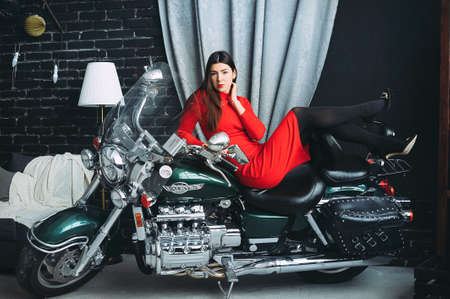 Slender young girl with bright make up in flat red dress sitting in profile on old motorbike in garage in pose