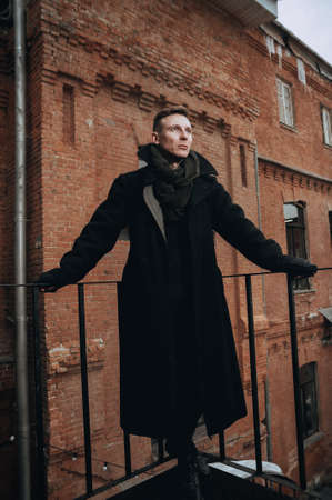 Portrait of a young man in a coat with a fur collar. On the background of a brick wall.
