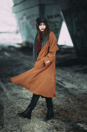 portrait of a beautiful girl in a brown coat under the bridge