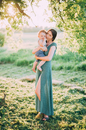 beautiful mother in a green dress with a child in nature. sunset light 版權商用圖片