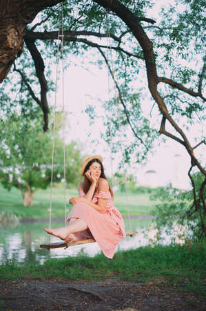 Beautiful happy girl in a pink dress relaxes on a swing against the backdrop of the lake. Summer holiday vacation travel trip