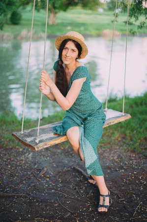 beautiful girl in a green dress and hat is resting on a swing against the backdrop of the lake