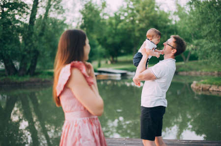 family with a small child on the lake. mom and dad walk in nature with his son Standard-Bild - 122599037