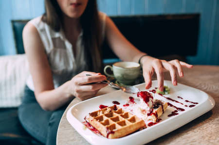 girl eating waffles with jam and ice cream. close-up