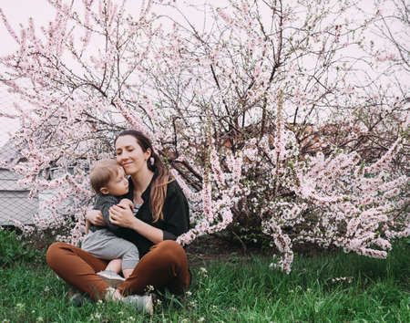 mother with little baby girl outdoors in blooming garden. woman holding daughter of one year old. 版權商用圖片