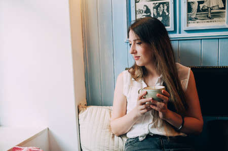 girl with a cup of coffee near the window in a cafe. lick your fingers