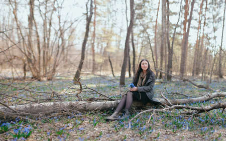 beautiful girl in a coat sitting on a log on the background of snowdrops. Spring