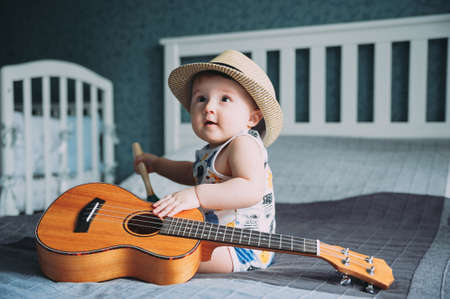A portrait of very cute 1 year old baby with musician looks wearing hat and holding small guitar or ukulele sitting on bed