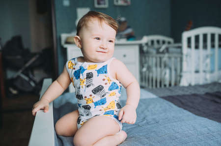 one year old baby boy sitting on a bed at home