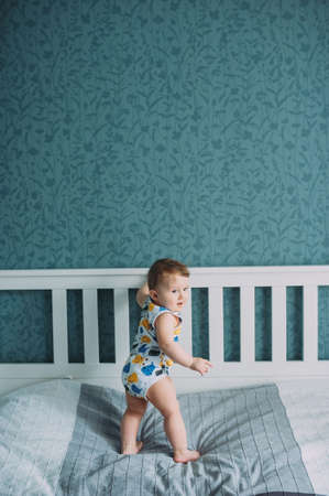 one year old baby boy standing on a bed at home