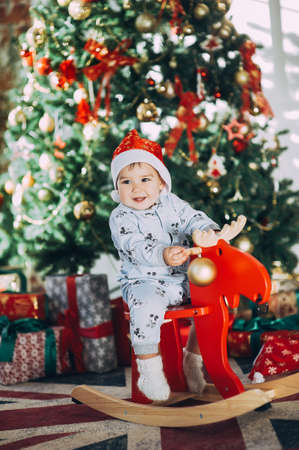 little baby boy in a Christmas cap sitting on a wooden horse by the Christmas tree Stock Photo - 123047556