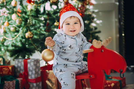 little baby boy in a Christmas cap sitting on a wooden horse by the Christmas tree Stock Photo