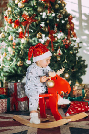 little baby boy in a Christmas cap sitting on a wooden horse by the Christmas tree Stock Photo - 123047716