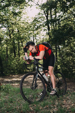 tired cyclist is resting in the forest. wearing a helmet and a red T-shirt