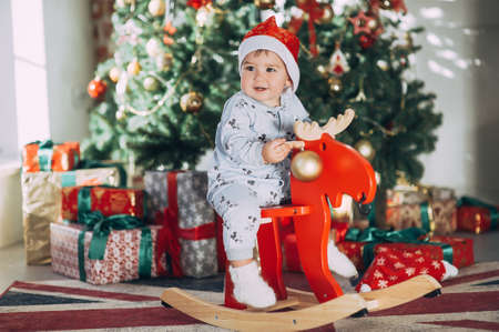 little baby boy in a Christmas cap sitting on a wooden horse by the Christmas tree Stock Photo - 123047733