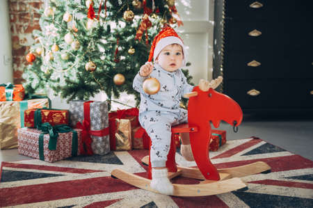 little baby boy in a Christmas cap sitting on a wooden horse by the Christmas tree Stock Photo - 123047788