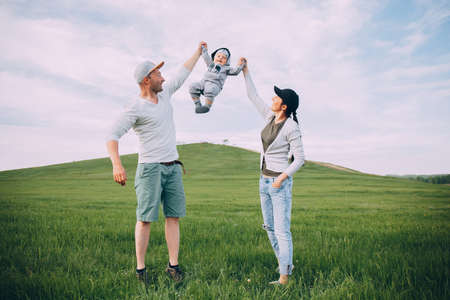 Happy parents throw up a child in nature on a green field. The concept of happiness, family Active lifestyle, family time