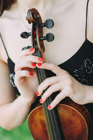 Beautiful girl holding a vintage violin in her hands. close-up Zdjęcie Seryjne - 124145829