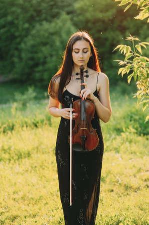 Beautiful girl with a violin on nature. long hair Zdjęcie Seryjne - 124145830