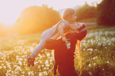 mother with a small child in a dandelion field at sunset. mother holds baby in her arms Zdjęcie Seryjne - 124145844