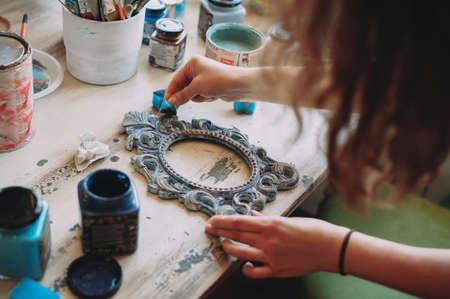 girl paints the frame with a brush. handwork. creation Zdjęcie Seryjne - 124145846