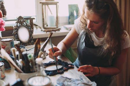girl paints the frame with a brush. handwork. creation Zdjęcie Seryjne - 124145853