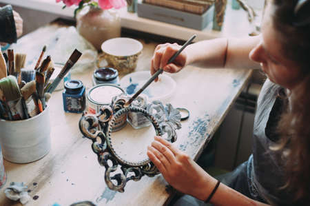 girl paints the frame with a brush. handwork. creation
