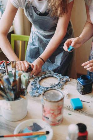 girl paints the frame with a brush. handwork. creation Zdjęcie Seryjne - 124145856